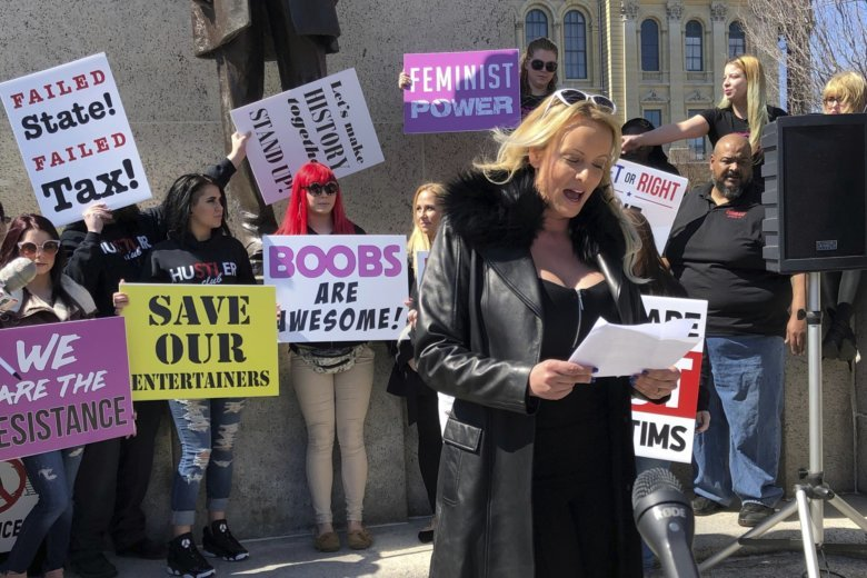 Adult film star Stormy Daniels reads a statement, protesting the Illinois  surcharge on live adult entertainment centers, beneath the statue of.