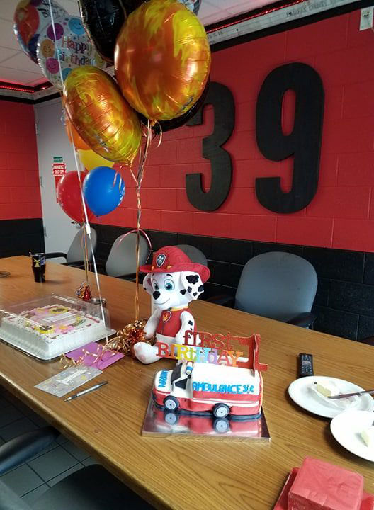"""The birthday bash included a """"Happy First Birthday Lauryn"""" sign outside the fire station, two cakes (one shaped like a miniature fire truck), balloons and a photo shoot with Lauryn and mom by a fire truck. (Courtesy Fairfax County Fire and Rescue)"""