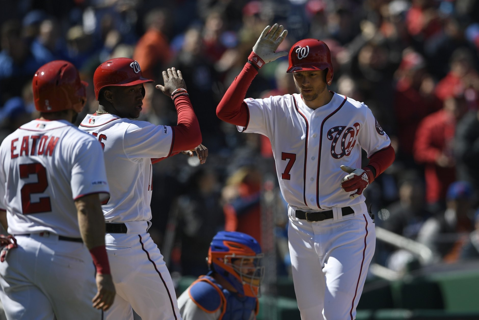 Washington Nationals' Trea Turner (7) celebrates his three-run home run with Victor Robles, center, and Adam Eaton (2) during the third inning of a baseball game against the New York Mets, Sunday, March 31, 2019, in Washington. (AP Photo/Nick Wass)