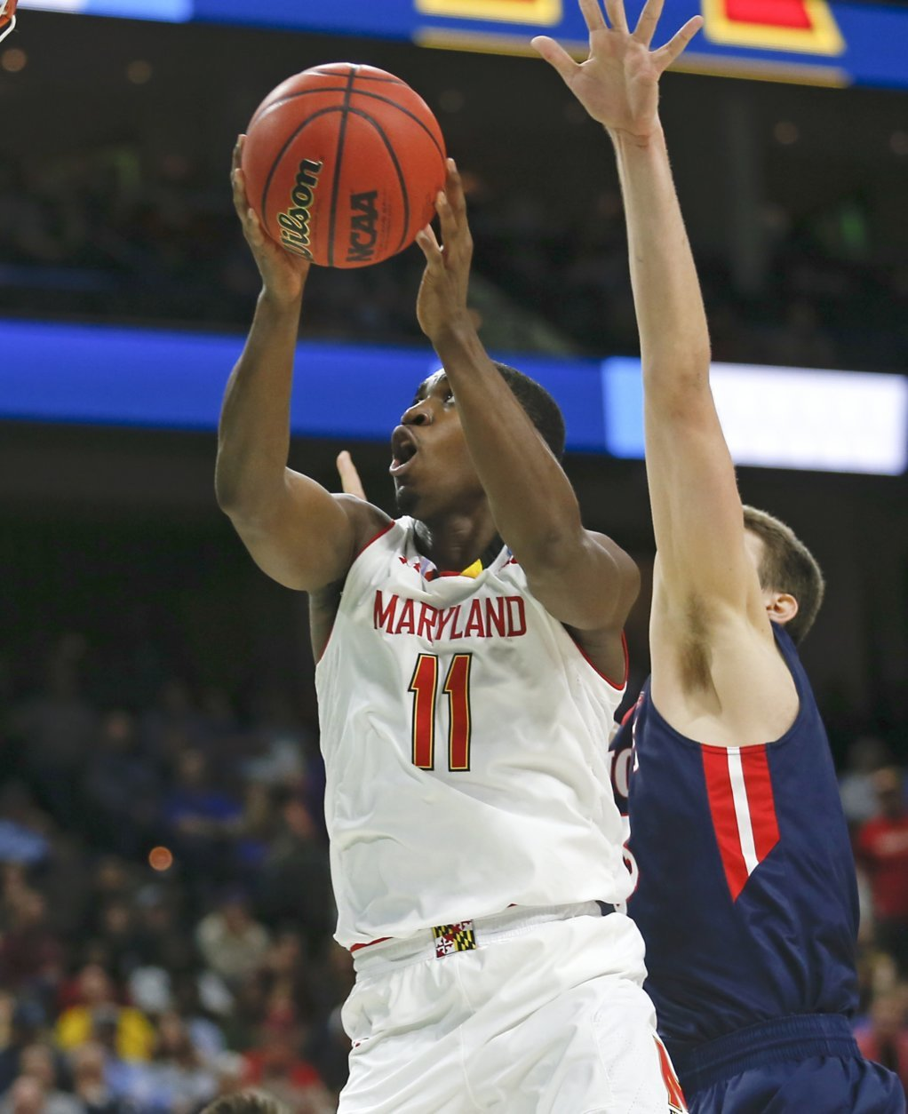 Maryland 's Darryl Morsell (11) goes up to shoot past Belmont 's Nick Muszynski during the first half of a first round men's college basketball game in the NCAA Tournament in Jacksonville, Fla., Thursday, March 21, 2019. (AP Photo/Stephen B. Morton)