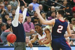 Maryland 's Serrel Smith Jr., center, passes the ball around Belmont 's Grayson Murphy (2) as Belmont head coach Rick Boyd stands back to avoid interference during the first half of a first round men's college basketball game in the NCAA Tournament in Jacksonville, Fla., Thursday, March 21, 2019. (AP Photo/Stephen B. Morton)