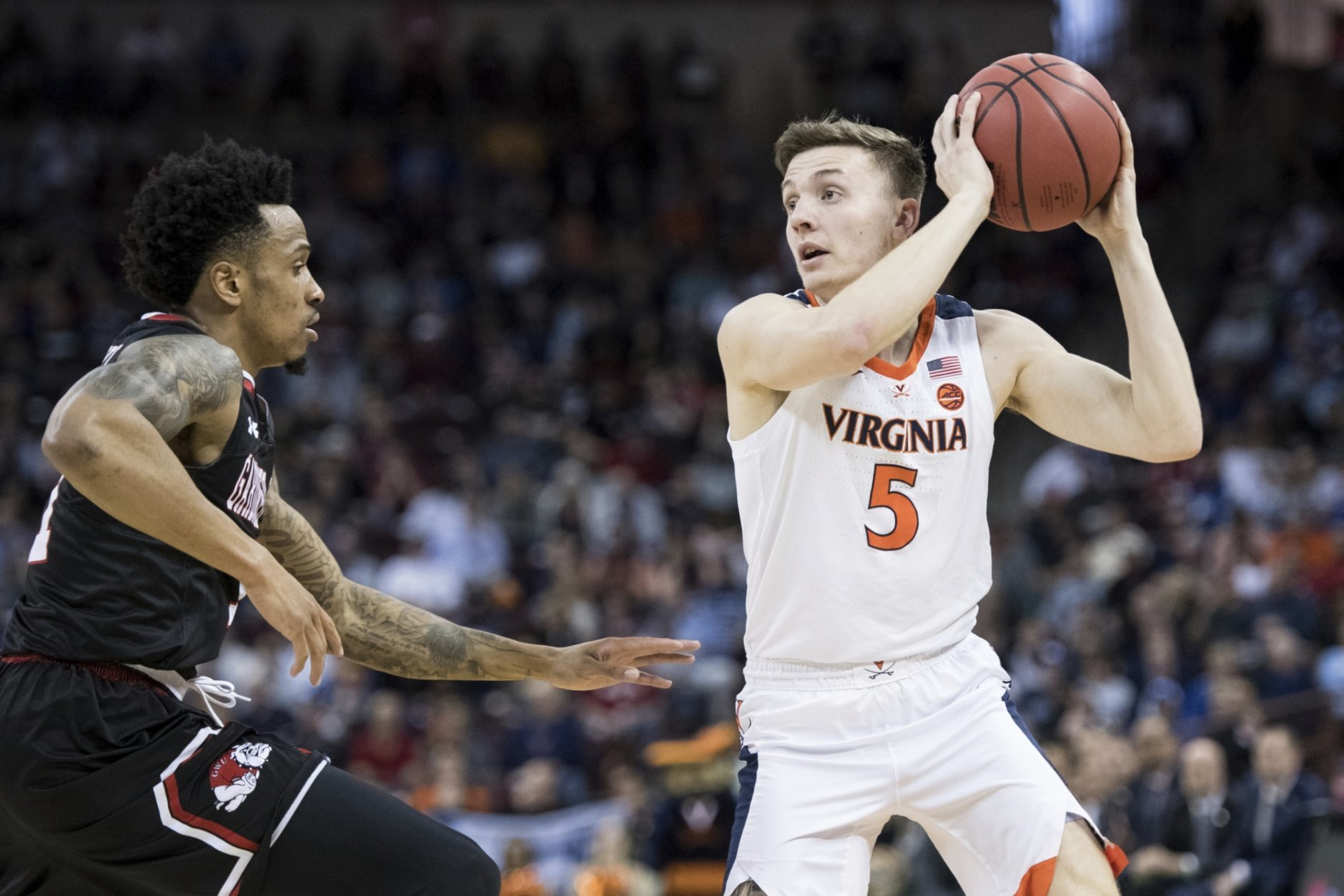 Virginia guard Kyle Guy (5) looks for a teammate as Gardner-Webb guard David Efianayi, left, defends during a first-round game in the NCAA men's college basketball tournament Friday, March 22, 2019, in Columbia, S.C. (AP Photo/Sean Rayford)
