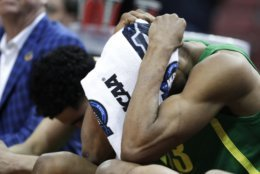 Oregon's Francis Okoro sits on the bench during the final minutes of the second half of a men's NCAA Tournament college basketball South Regional semifinal game against Virginia, Friday, March 29, 2019, in Louisville, Ky. Virginia won 53-49. (AP Photo/Michael Conroy)
