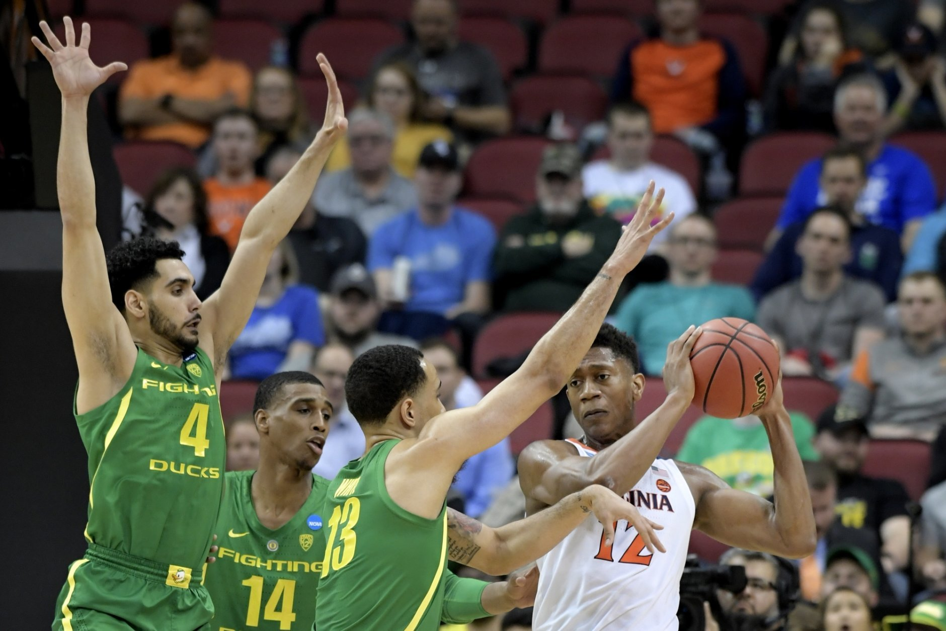 Virginia's De'Andre Hunter (12) is defended by Oregon's Ehab Amin (4), Kenny Wooten (14) and Paul White (13) during the first half of a men's NCAA Tournament college basketball South Regional semifinal game, Thursday, March 28, 2019, in Louisville, Ky. (AP Photo/Timothy D. Easley)