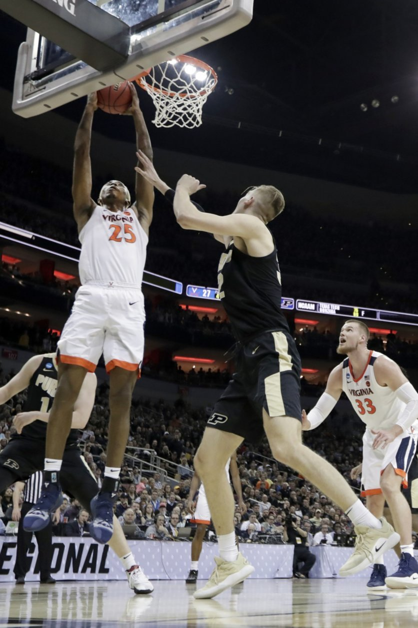 Virginia's Mamadi Diakite (25) puts up a shot against Purdue's Matt Haarms, center, as Virginia's Jack Salt (33) watches during the first half of the men's NCAA Tournament college basketball South Regional final game, Saturday, March 30, 2019, in Louisville, Ky. (AP Photo/Michael Conroy)