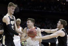 Virginia's Kyle Guy, middle, goes to the basket against Purdue's Ryan Cline, right, and Matt Haarms (32) during the first half of the men's NCAA Tournament college basketball South Regional final game, Saturday, March 30, 2019, in Louisville, Ky. (AP Photo/Michael Conroy)