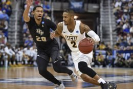 VCU's Marcus Evans (2) drives against Central Florida's Frank Bertz (20) during a first-round game in the NCAA men's college basketball tournament Friday, March 22, 2019, in Columbia, S.C. (AP Photo/Richard Shiro)