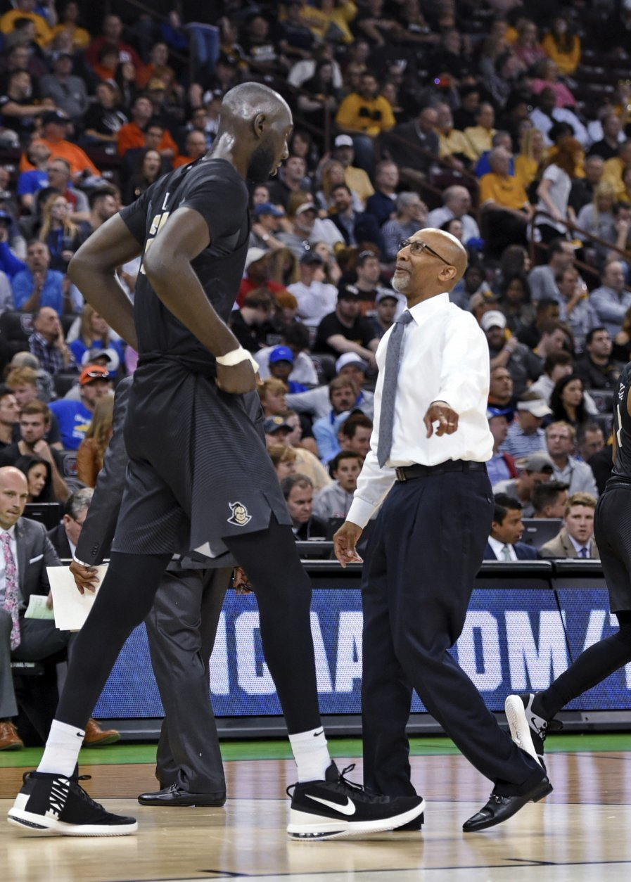 Central Florida coach Johnny Dawkins, right, speaks to Tako Fall during a first-round game in the NCAA men's college basketball tournament Friday, March 22, 2019, in Columbia, S.C.(AP Photo/Richard Shiro)