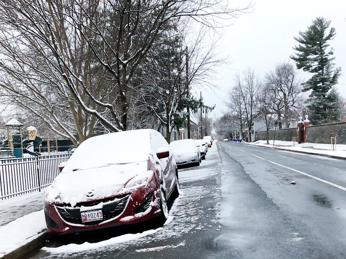 Snow left a thin blanket of white over cars in Frederick, Maryland. (WTOP/Neal Augenstein)