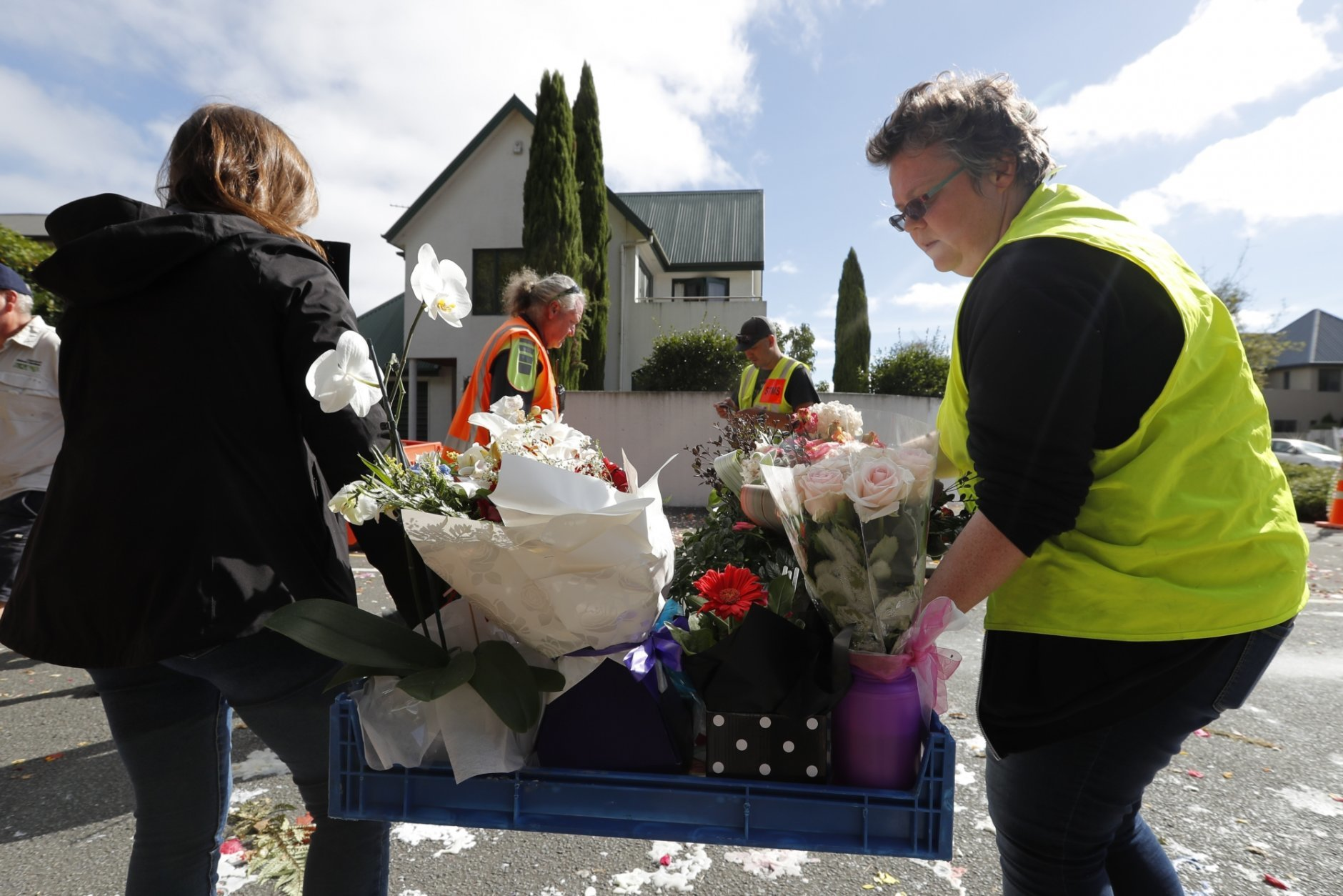 Volunteers move flowers away near the Al Noor mosque in Christchurch, New Zealand, Thursday, March 21, 2019. Thousands of people were expected to come together for an emotional Friday prayer service led by the imam of one of the two New Zealand mosques where 50 worshippers were killed in a white supremacist attack on Friday March 15. (AP Photo/Vincent Thian)
