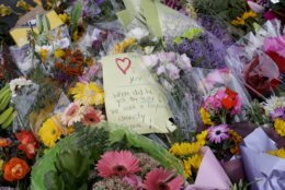 A handwritten message is placed at a makeshift memorial near the Masjid Al Noor mosque in Christchurch, New Zealand, Saturday, March 16, 2019, where one of the two mosque mass shootings at occurred. (AP Photo/Mark Baker)