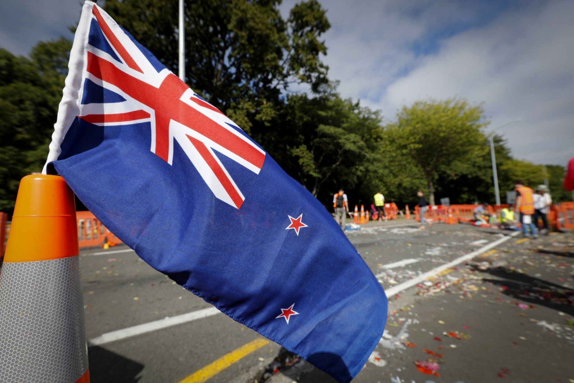 New Zealand's flag is on display as volunteers move flowers away near the Al Noor mosque in Christchurch, New Zealand, Thursday, March 21, 2019. Thousands of people were expected to come together for an emotional Friday prayer service led by the imam of one of the two New Zealand mosques where 50 worshippers were killed in a white supremacist attack on Friday March 15. (AP Photo/Vincent Thian)