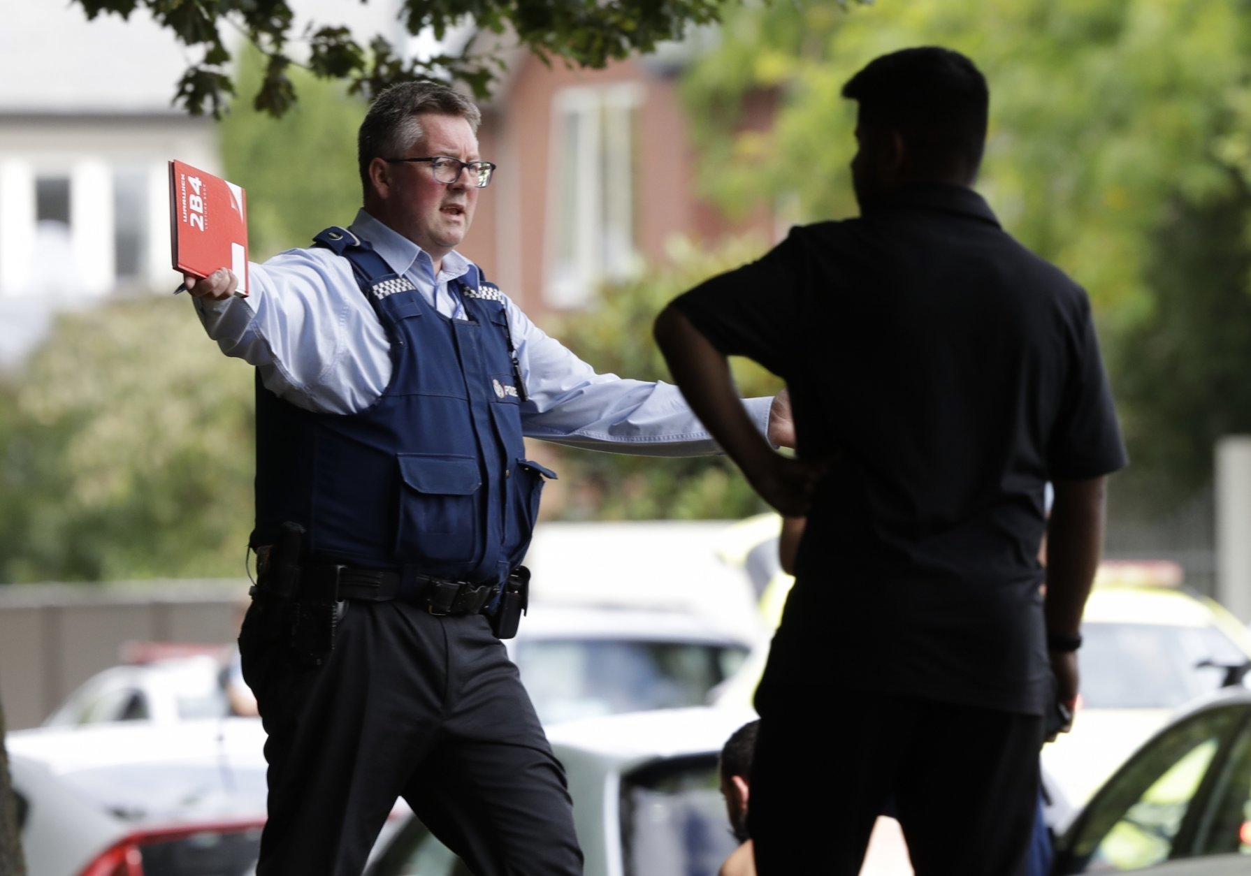 A police officer attempts to move people away from across the road from a mosque in central Christchurch, New Zealand, Friday, March 15, 2019. A witness says a number of people have been killed in a mass shooting at a mosque in the New Zealand city of Christchurch. Police urge people to stay indoors.(AP Photo/Mark Baker)
