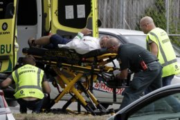 Ambulance staff take a man from outside a mosque in central Christchurch, New Zealand, Friday, March 15, 2019.  A witness says many people have been killed in a mass shooting at a mosque in the New Zealand city of Christchurch. (AP Photo/Mark Baker)
