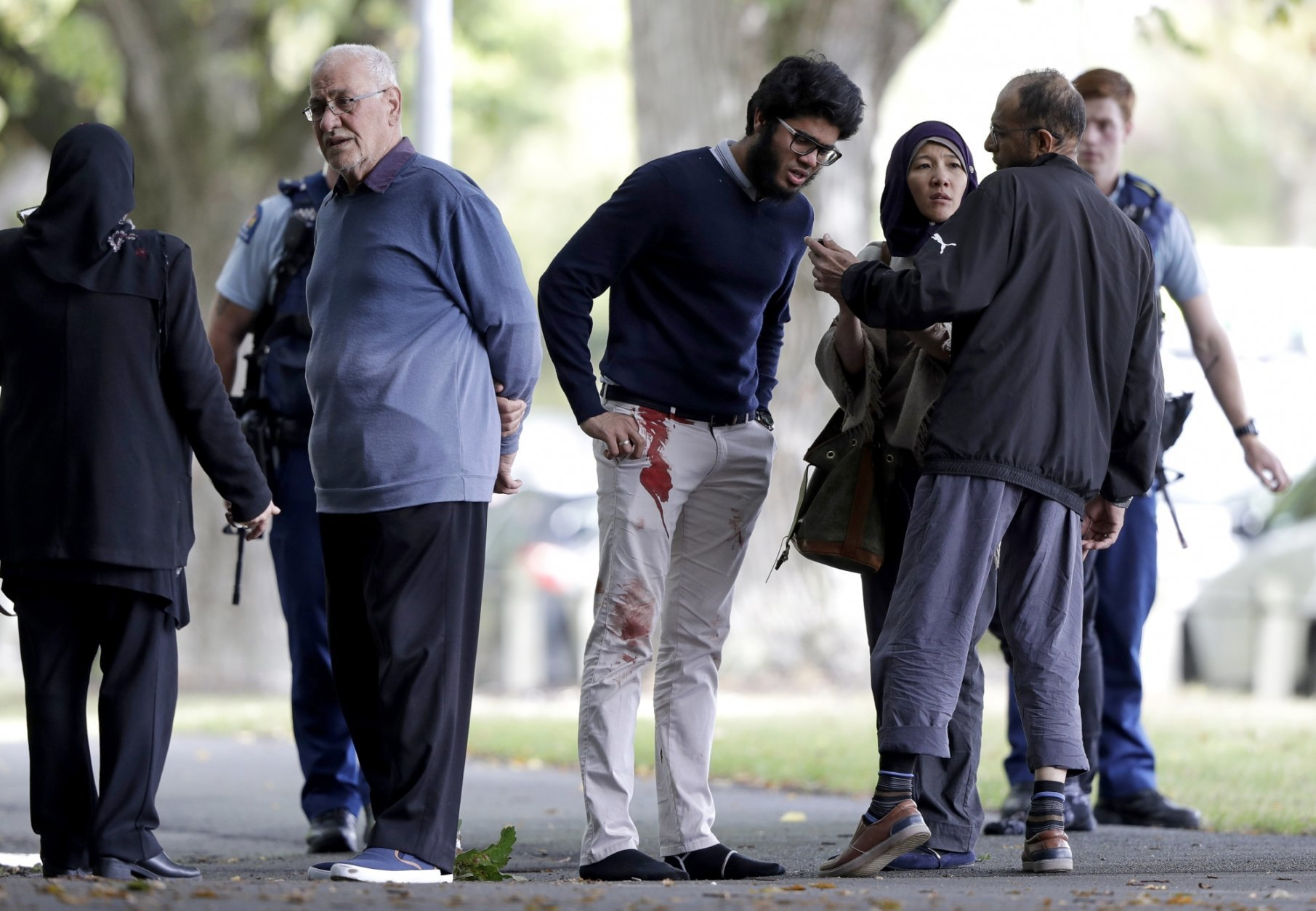 People stand across the road from a mosque in central Christchurch, New Zealand, Friday, March 15, 2019. A witness says a number of people have been killed in a mass shooting at a mosque in the New Zealand city of Christchurch; police urge people to stay indoors.(AP Photo/Mark Baker)