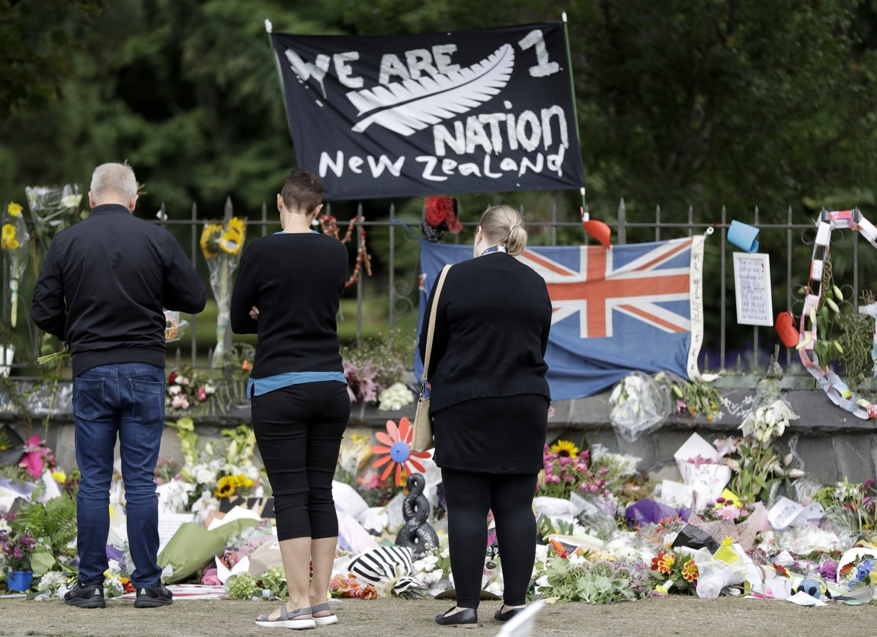 Visitors to the Botanical Gardens look at a floral tribute for the mosque shootings in Christchurch, New Zealand, Thursday, March 21, 2019. Thousands of people were expected to come together for an emotional Friday prayer service led by the imam of one of the two New Zealand mosques where 50 worshippers were killed in a white supremacist attack on Friday March 15. (AP Photo/Mark Baker)