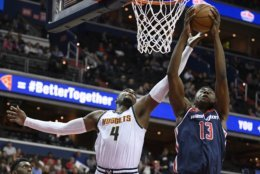 Washington Wizards center Thomas Bryant (13) grabs a rebound next to Denver Nuggets forward Paul Millsap (4) during the first half of an NBA basketball game Thursday, March 21, 2019, in Washington. (AP Photo/Nick Wass)