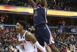 Washington Wizards center Thomas Bryant (13) dunks against Denver Nuggets guard Gary Harris (14) during the second half of an NBA basketball game Thursday, March 21, 2019, in Washington. The Nuggets won 113-108. (AP Photo/Nick Wass)