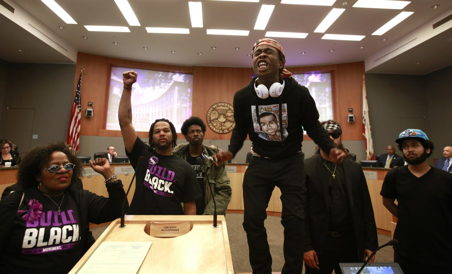 FILE - In this Tuesday, March 27, 2018 file photo, Stevante Clark stands on a desk as he shouts the name of his brother Stephon Clark, who was fatally shot by police a week earlier, during a meeting of the Sacramento City Council in Sacramento, Calif. Prosecutors are expected to announce Saturday, March 1 whether two police officers will face charges in last year's fatal shooting in Sacramento of an unarmed black man that generated nationwide protests. (AP Photo/Rich Pedroncelli, File)