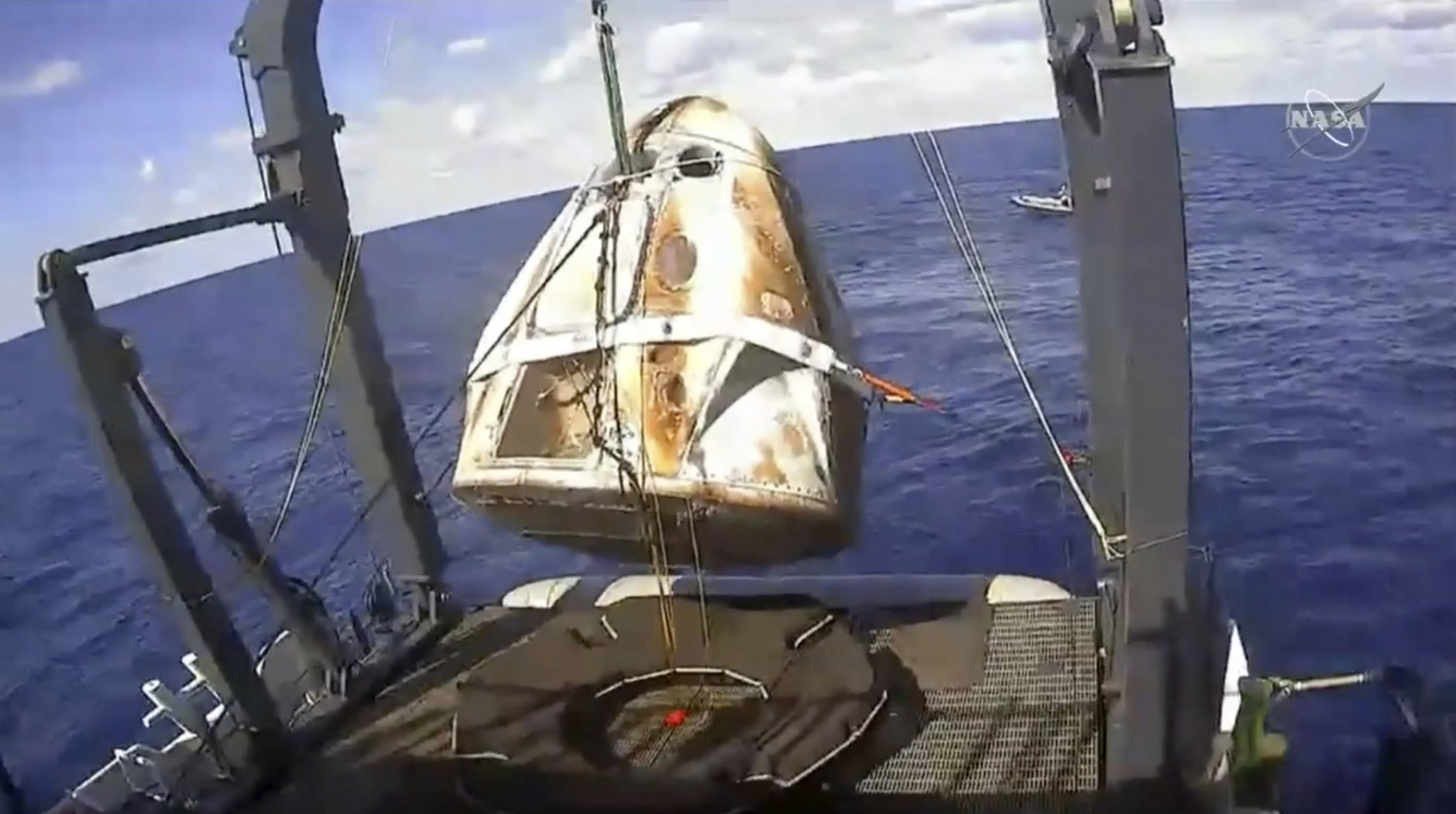 In this image from video made available by NASA, the SpaceX Crew Dragon capsule is hoisted onto a ship in the Atlantic Ocean off the Florida coast after it returned from a mission to the International Space Station. It marks the first time in 50 years that a capsule designed for astronauts returned from space by splashdown in the ocean. (NASA via AP)