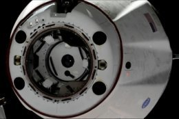 In this image taken from NASA Television, SpaceX's swanky new crew capsule undocks from the International Space Station, left, Friday, March 8, 2019. The capsule undocked and is headed toward an old-fashioned splashdown. The Dragon capsule pulled away from the orbiting lab early Friday, a test dummy named Ripley its lone occupant. (NASA TV via AP)