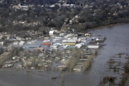 This March 17, 2019 photo released by the U.S. Air Force shows an aerial view of Areas surrounding Offutt Air Force Base affected by flood waters in Neb. Surging unexpectedly strong and up to 7 feet high, the Missouri River floodwaters that poured on to much the Nebraska air base that houses the U.S. Strategic Command overwhelmed the frantic sandbagging by troops and their scramble to save sensitive equipment, munitions and aircraft. (Tech. Sgt. Rachelle Blake/The U.S. Air Force via AP)