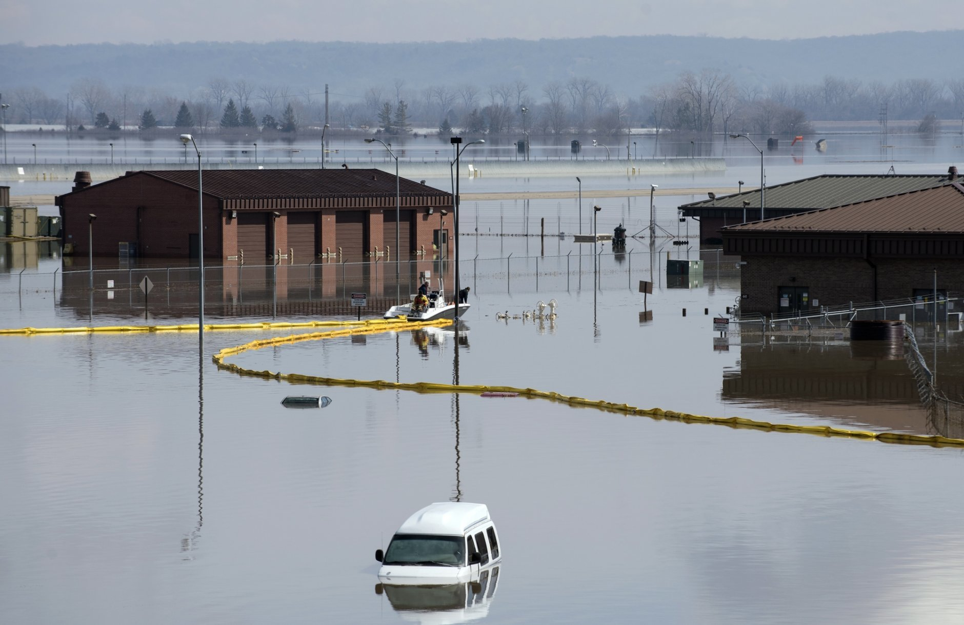 In this March 18, 2019 photo released by the U.S. Air Force, environmental restoration employees deploy a containment boom from a boat on Offutt Air Force Base in Neb., as a precautionary measure for possible fuel leaks in the flooded area. Surging unexpectedly strong and up to 7 feet high, the Missouri River floodwaters that poured on to much the Nebraska air base that houses the U.S. Strategic Command overwhelmed the frantic sandbagging by troops and their scramble to save sensitive equipment, munitions and aircraft. (Delanie Stafford, The U.S. Air Force via AP)