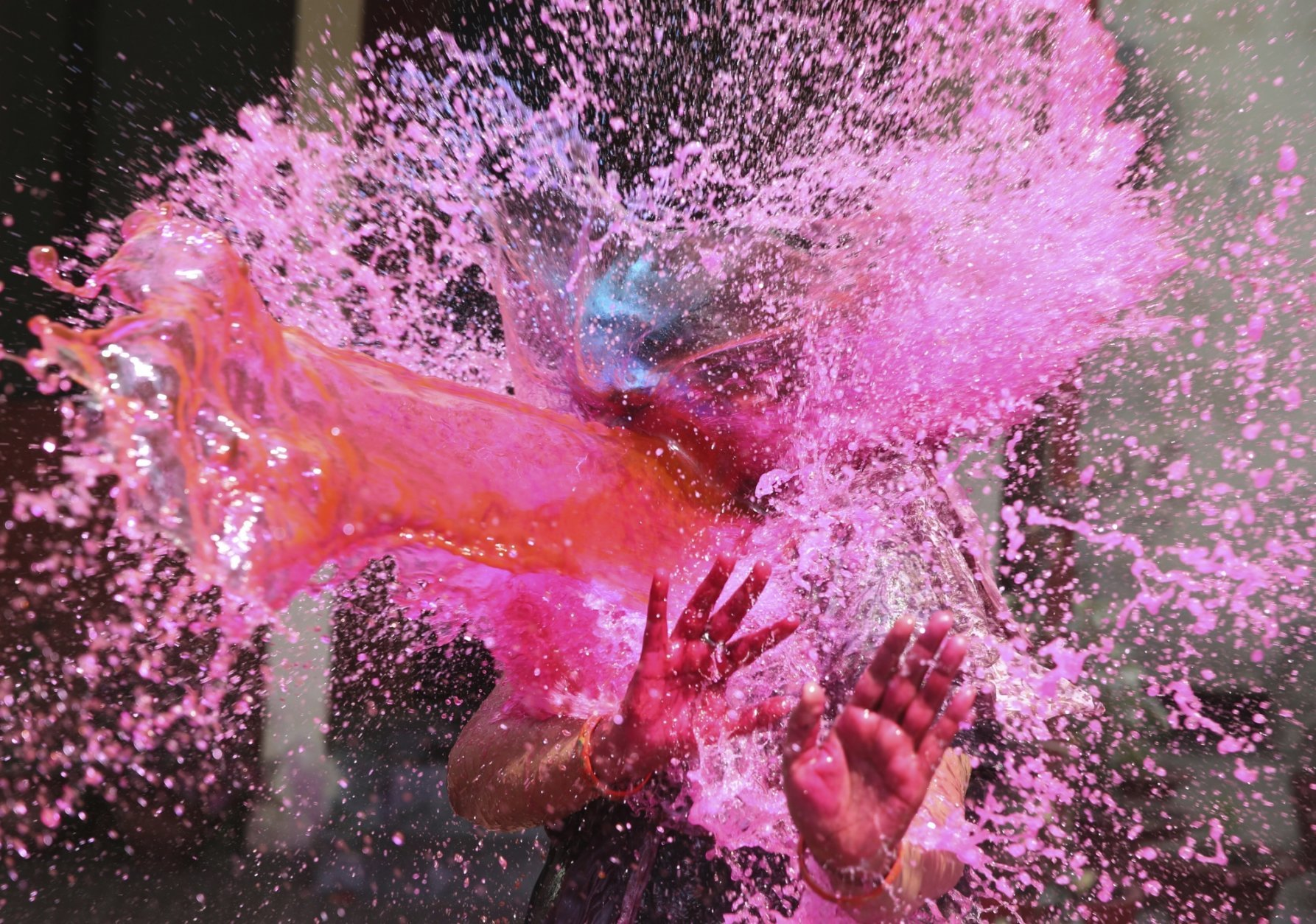 In this Thursday, March 21, 2019, file photo, a girl gestures with her hands as colored water is splashed on her during celebrations marking Holi festival in Allahabad, India. Holi, the festival of colors, also marks the advent of spring. (AP Photo/Rajesh Kumar Singh, File)