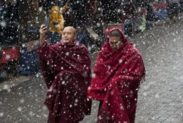 In this Wednesday, Feb. 27, 2019, photo, an exile Tibetan Buddhist monk uses his phone camera as he walks with another in the snow in Dharmsala, India. This Himalayan region saw another snowfall on Wednesday. (AP Photo/Ashwini Bhatia, File)