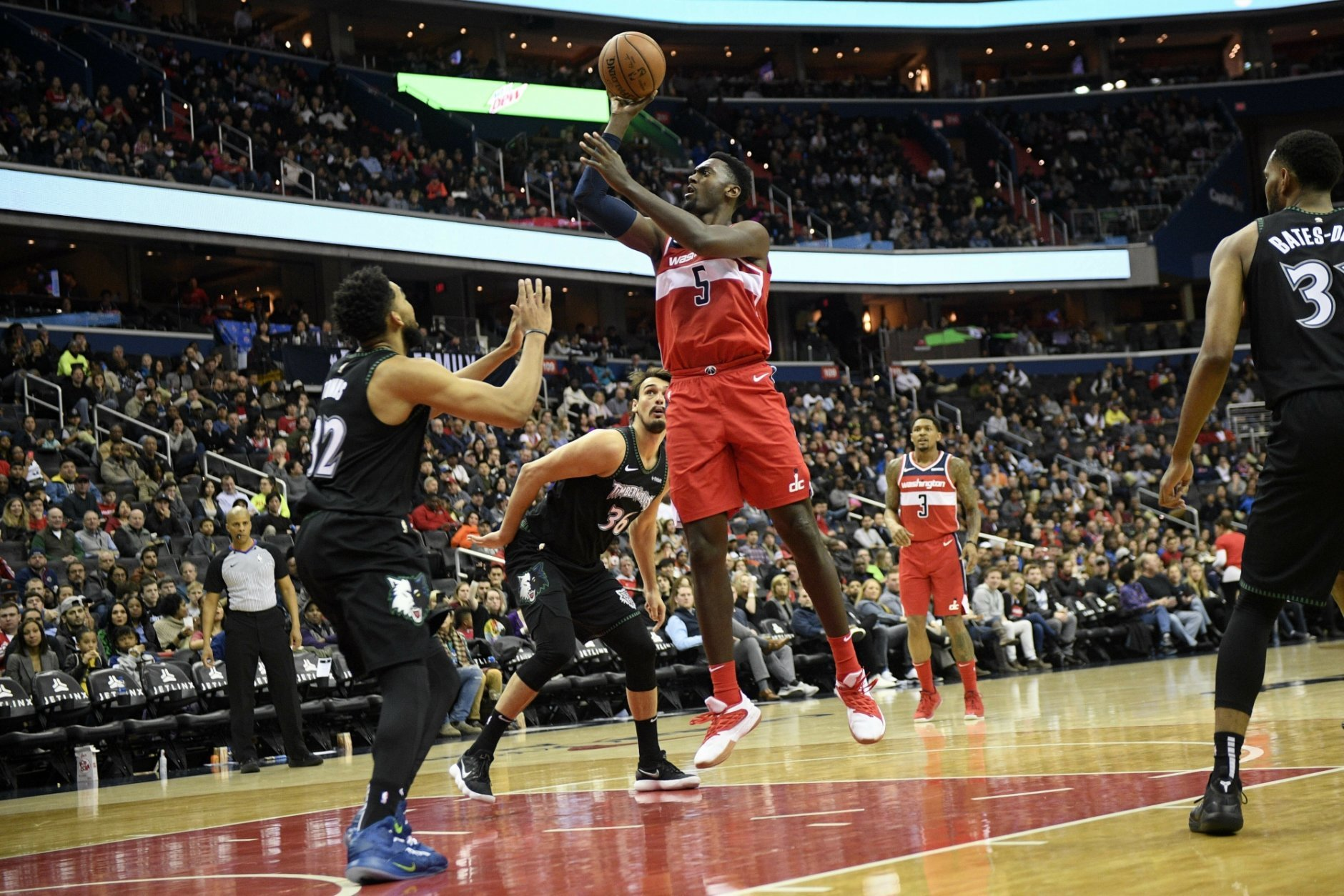 Washington Wizards forward Bobby Portis (5) shoots against Minnesota Timberwolves center Karl-Anthony Towns (32) and forward Dario Saric (36) during the second half of an NBA basketball game, Sunday, March 3, 2019, in Washington. Also seen is Wizards guard Bradley Beal (3). The Wizards won 135-121. (AP Photo/Nick Wass)