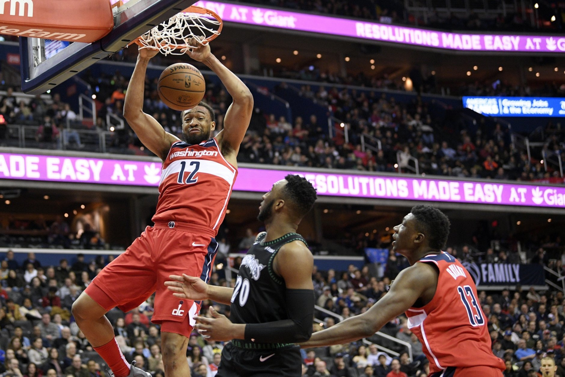 Washington Wizards forward Jabari Parker (12) dunks over Minnesota Timberwolves guard Josh Okogie (20) during the second half of an NBA basketball game, Sunday, March 3, 2019, in Washington. Also seen is Wizards center Thomas Bryant (13). The Wizards won 135-121. (AP Photo/Nick Wass)