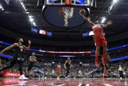 Washington Wizards guard Bradley Beal (3) goes to the basket against Minnesota Timberwolves guard Derrick Rose (25), center Karl-Anthony Towns (32) and guard Jeff Teague, second from left, during the first half of an NBA basketball game, Sunday, March 3, 2019, in Washington. The Wizards won 135-121. (AP Photo/Nick Wass)
