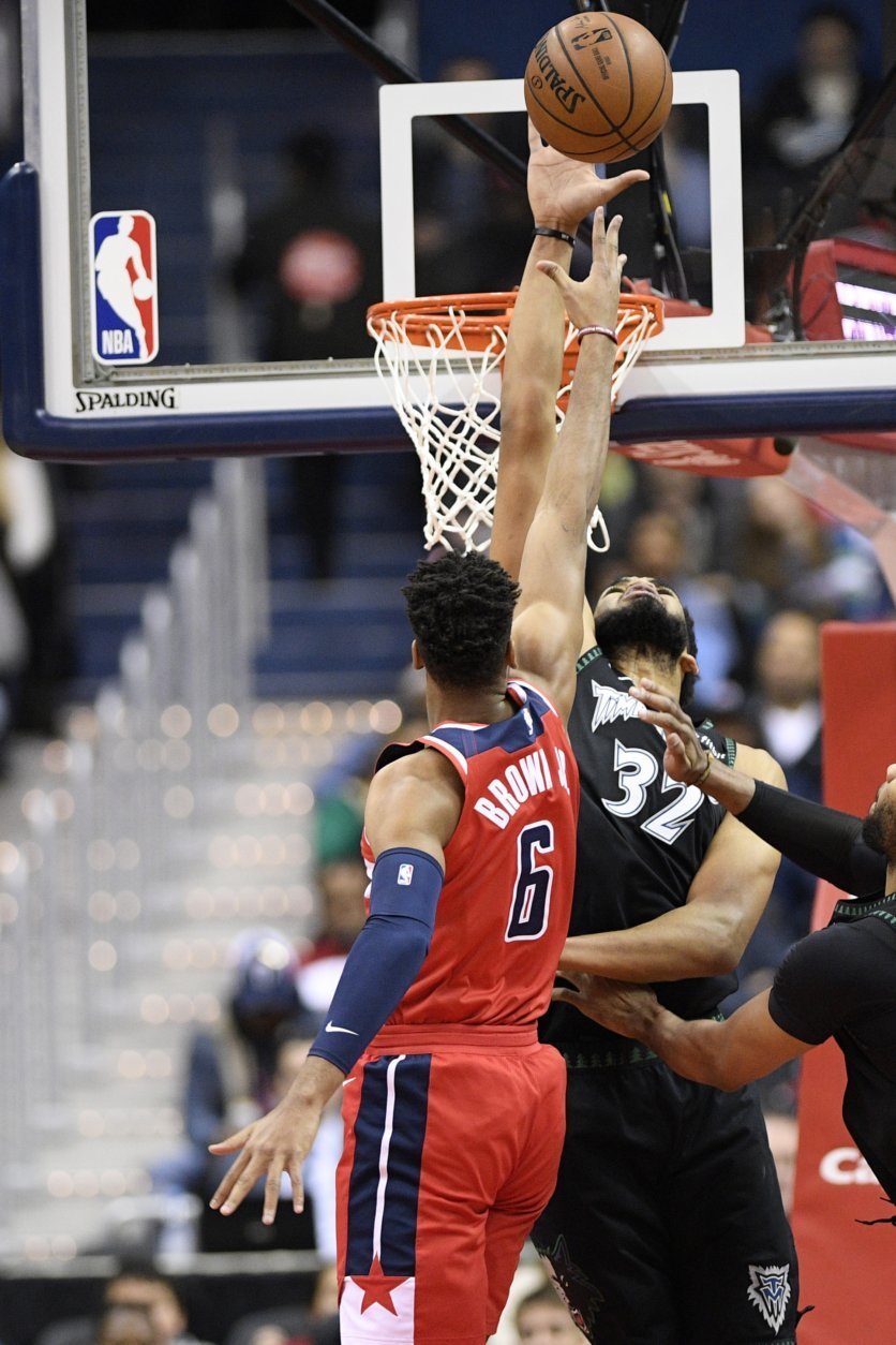 Minnesota Timberwolves center Karl-Anthony Towns (32) blocks Washington Wizards forward Troy Brown Jr. (6) during the first half of an NBA basketball game, Sunday, March 3, 2019, in Washington. (AP Photo/Nick Wass)