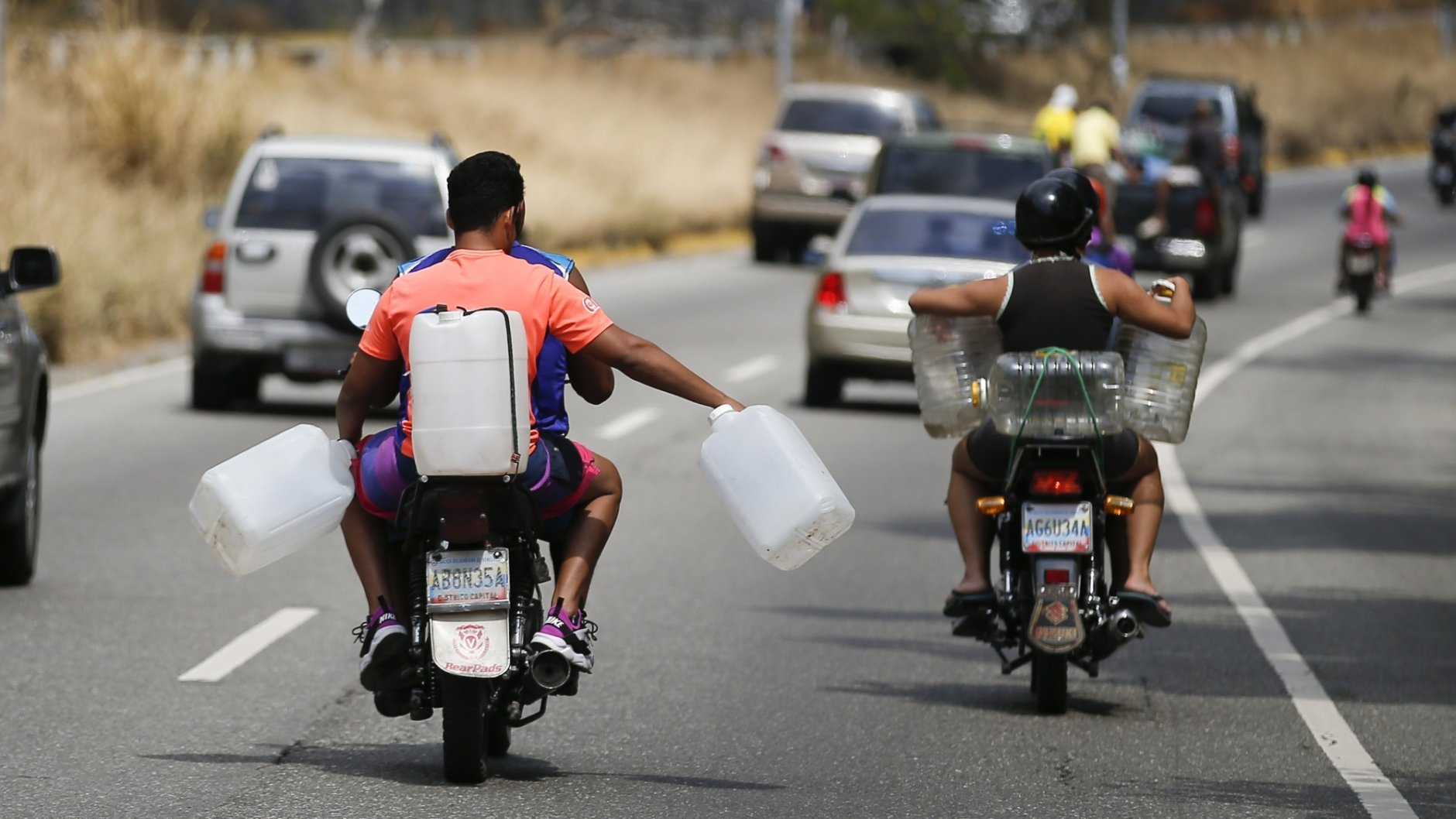 Motorcyclists carry empty containers to collect water, during rolling blackouts affecting the water pumps in people's homes and apartment buildings, in Caracas, Venezuela, Sunday, March 10, 2019.  Venezuelans reached new levels of desperation Sunday as the country's worst blackouts took their toll, gathering in larger numbers than usual to collect water and scrounging for scarce cash to pay for food in the few shops that were open. (AP Photo/Eduardo Verdugo)
