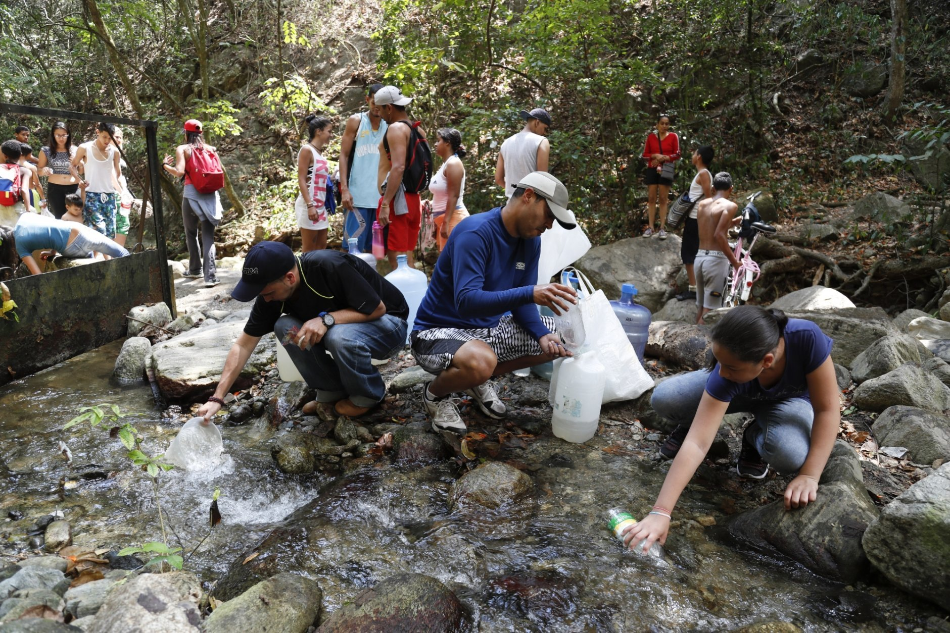 People collect water from a stream in Avila National Park during rolling blackouts, which affects the water pumps in people's homes and apartment buildings, in Caracas, Venezuela, Sunday, March 10, 2019. Venezuelans reached new levels of desperation Sunday as the country's worst blackouts took their toll, gathering in larger numbers than usual at springs in the mountains of Caracas to collect water and scrounging for scarce cash to pay for food in the few shops that were open.  (AP Photo/Eduardo Verdugo)