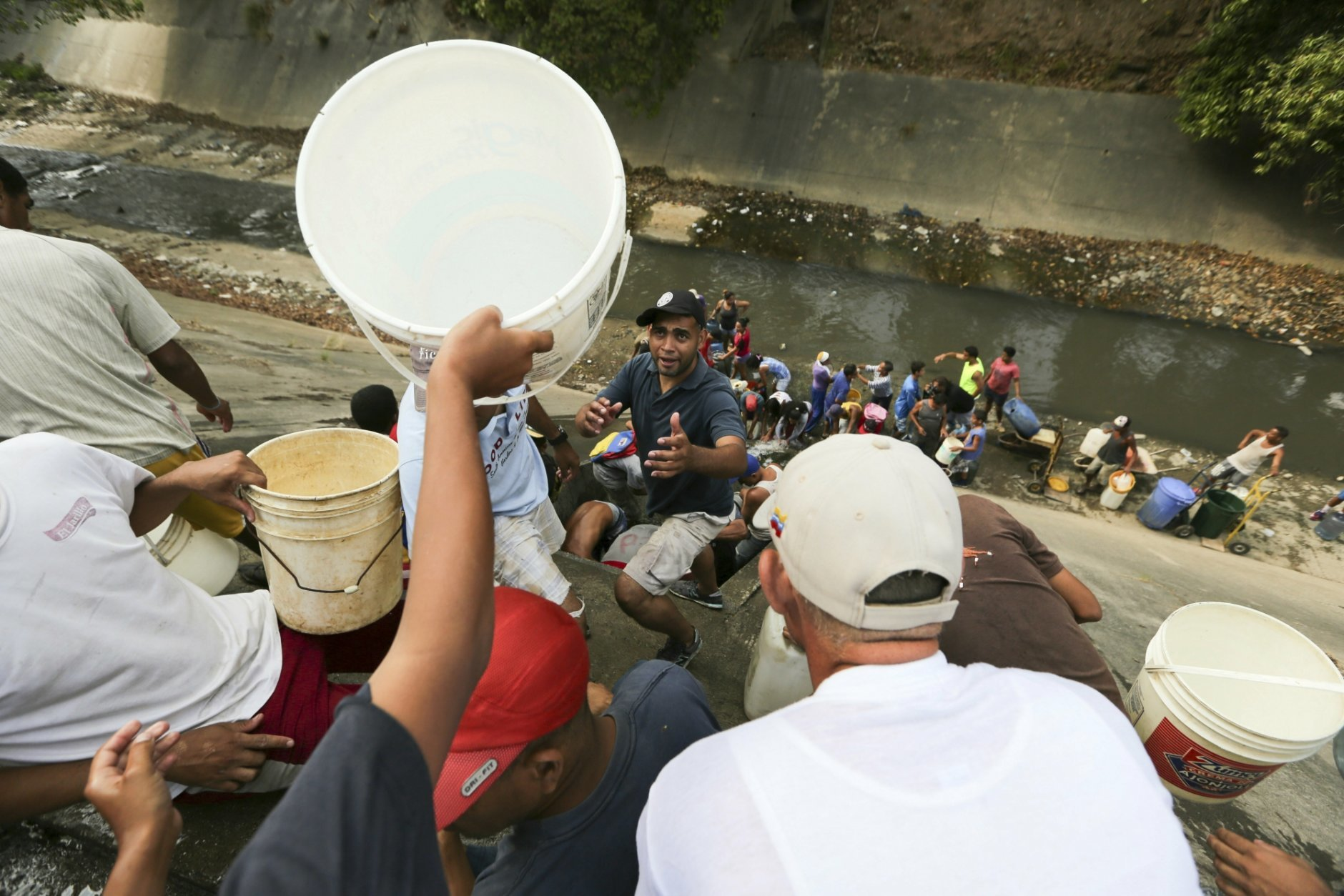 People collect water from a leaking pipeline above the Guaire River during rolling blackouts, which affects the water pumps in people's homes, offices and stores, in Caracas, Venezuela, Monday, March 11, 2019. The blackout has intensified the toxic political climate, with opposition leader Juan Guaido blaming alleged government corruption and mismanagement and President Nicolas Maduro accusing his U.S.-backed adversary of sabotaging the national grid. (AP Photo/Fernando Llano)