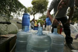 People fill containers with water from a public fountain during rolling blackouts which has kept people without running water in their homes in Caracas, Venezuela, Monday, March 11, 2019. The blackout has intensified the toxic political climate, with opposition leader Juan Guaido blaming alleged government corruption and mismanagement and President Nicolas Maduro accusing his U.S.-backed adversary of sabotaging the national grid. (AP Photo/Fernando Llano)