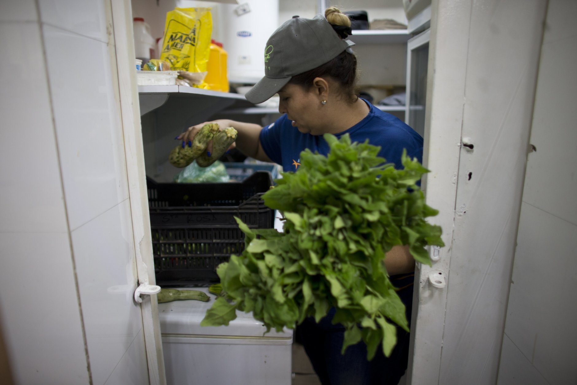 "A volunteer picks out vegetables donated by citizens whose food will spoil due to their refrigerators going without power during a blackout in Caracas, Venezuela, Monday, March 11, 2019. Hachebistro restaurant lent its kitchen to make ""arepas"" with food donated by residents whose refrigerators were without power, to be distributed to foundations, hospitals and those most in need. (AP Photo/Ariana Cubillos)"