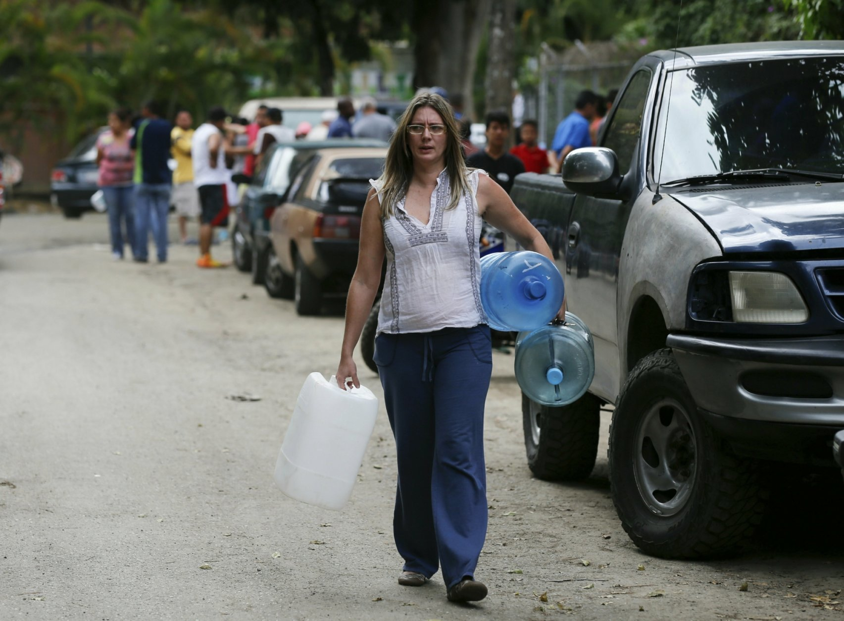 A woman carries empty containers to fill with water as people gather at a public fountain during rolling blackouts, which affects running water in people's homes, in Caracas, Venezuela, Monday, March 11, 2019. The blackout has intensified the toxic political climate, with opposition leader Juan Guaido blaming alleged government corruption and mismanagement and President Nicolas Maduro accusing his U.S.-backed adversary of sabotaging the national grid. (AP Photo/Fernando Llano)