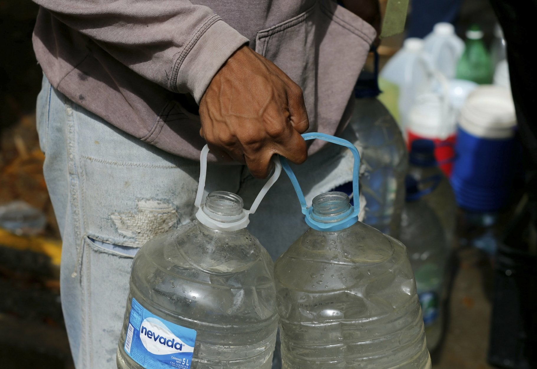 A man carries plastic bottles filled with water he collected from a pipeline left open, during rolling blackouts which affects the water pumps in people's homes, in Caracas, Venezuela, Monday, March 11, 2019. The blackout has intensified the toxic political climate, with opposition leader Juan Guaido blaming alleged government corruption and mismanagement and President Nicolas Maduro accusing his U.S.-backed adversary of sabotaging the national grid. (AP Photo/Fernando Llano)