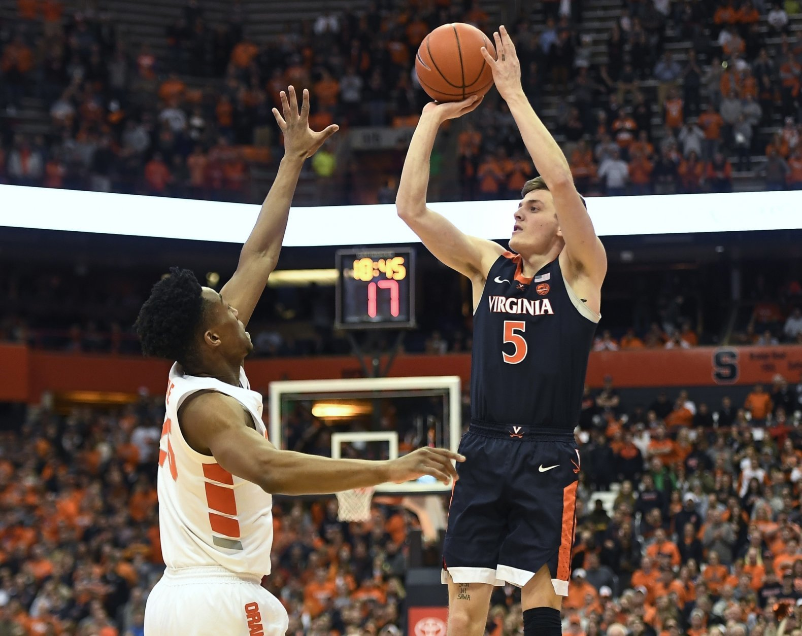 Virginia guard Kyle Guy, right, shoots over Syracuse guard Tyus Battle during the first half of an NCAA college basketball game in Syracuse, N.Y., Monday, March 4, 2019. (AP Photo/Adrian Kraus)