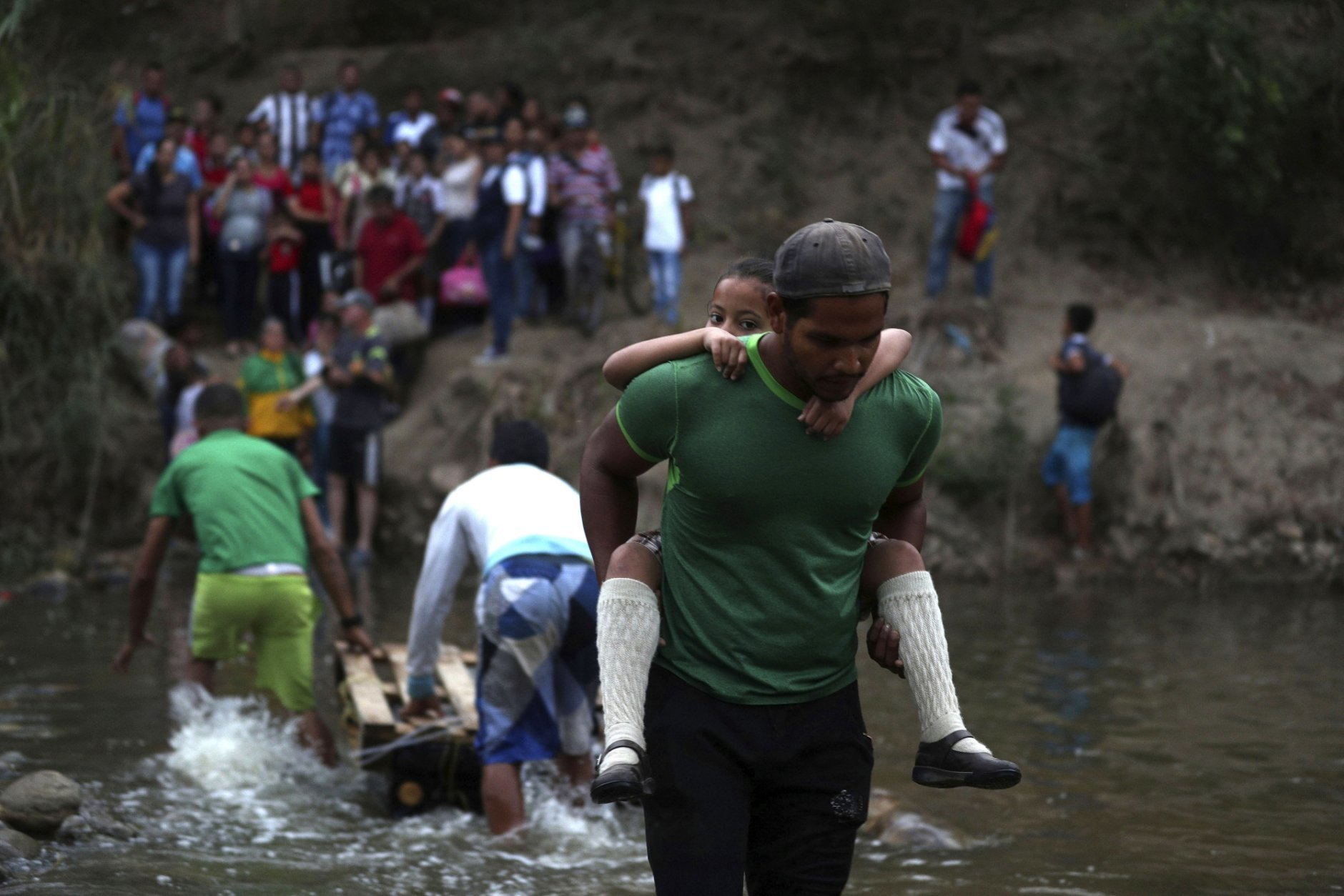 A volunteer gives a Venezuelan student a piggyback ride across the Tachira River into Colombia from Venezuela, near the Francisco de Paula Santander International Bridge which services Cucuta, Colombia, and has been closed by Venezuelan authorities, Wednesday, March 6, 2019. Many Venezuelan parents send children across the busy border, believing they will get a better education there. (AP Photo/Martin Mejia)