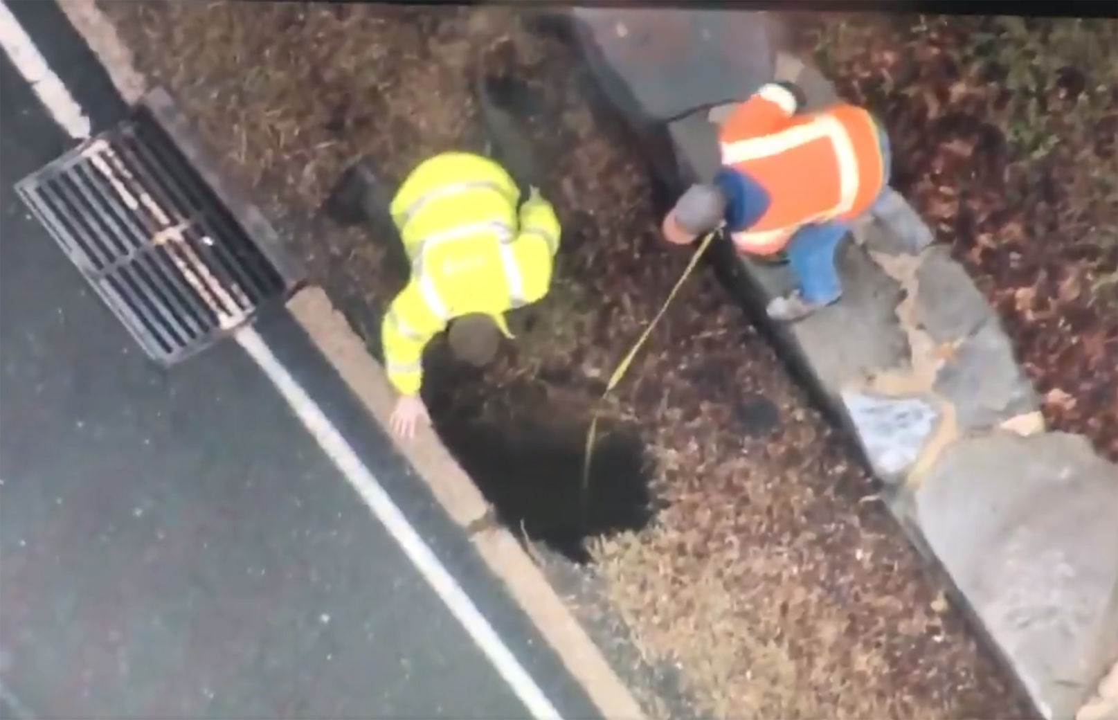 Workers measure a hole next to George Washington Parkway. (Courtesy NBC Washington/Twitter/@Chopper4Brad)