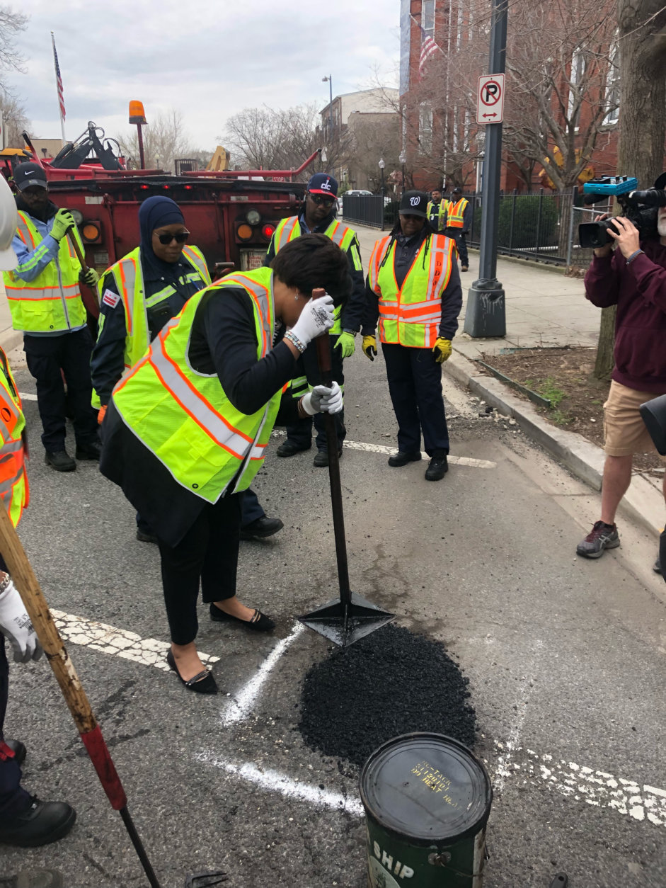 Mayor Muriel Bowser helps tamp down freshly scooped asphalt to fill a pothole on G St. NE. (WTOP/Max Smith)