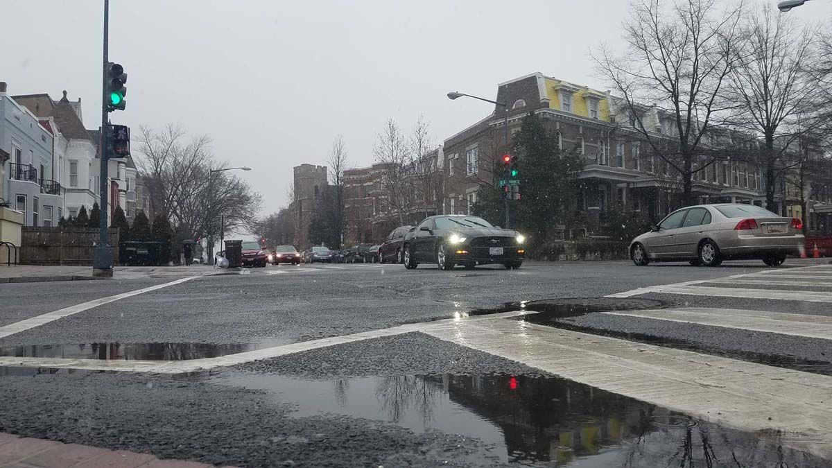 Snow falls on wet roads in Columbia Heights, D.C. (WTOP/Will Vitka)