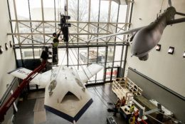 Contractors from iWeiss work to rig the X-45A drone for lowering in the Military Unmanned Aerial Vehicles (UAV) Gallery of the National Air and Space Museum in Washington, DC, February 22, 2019. (Smithsonian photo by Jim Preston)  Material is subject to Smithsonian Terms of Use. Should you wish to use National Air and Space material in any medium, please submit an Application for Permission to Reproduce NASM Material, available at:  https://airandspace.si.edu/permissions