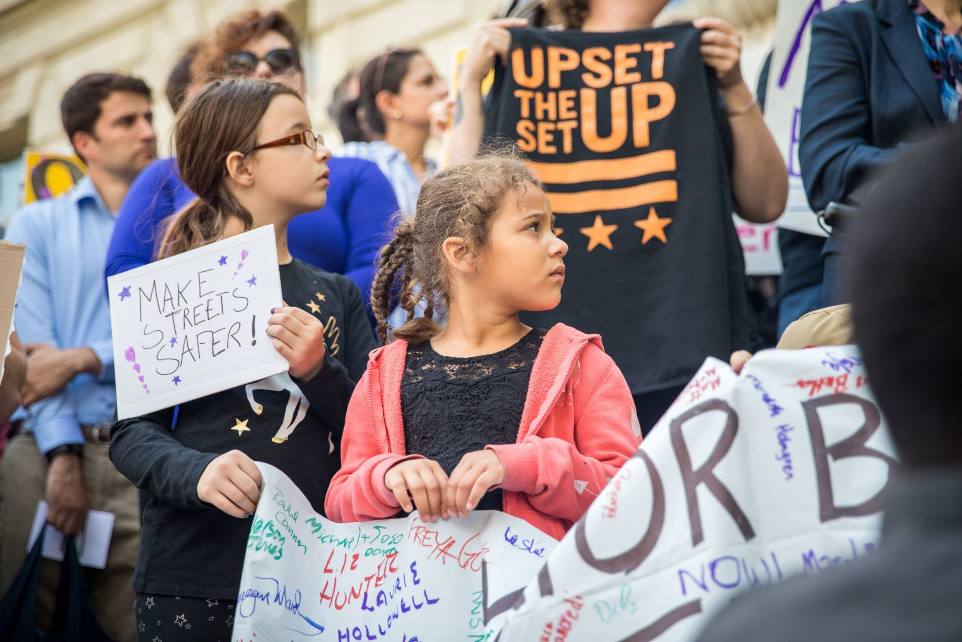 Demonstrators in front of the Wilson Building on Friday call for better infrastructure as one way to protect road users. (Courtesy Aimee Custis/Aimee Custis Photography)