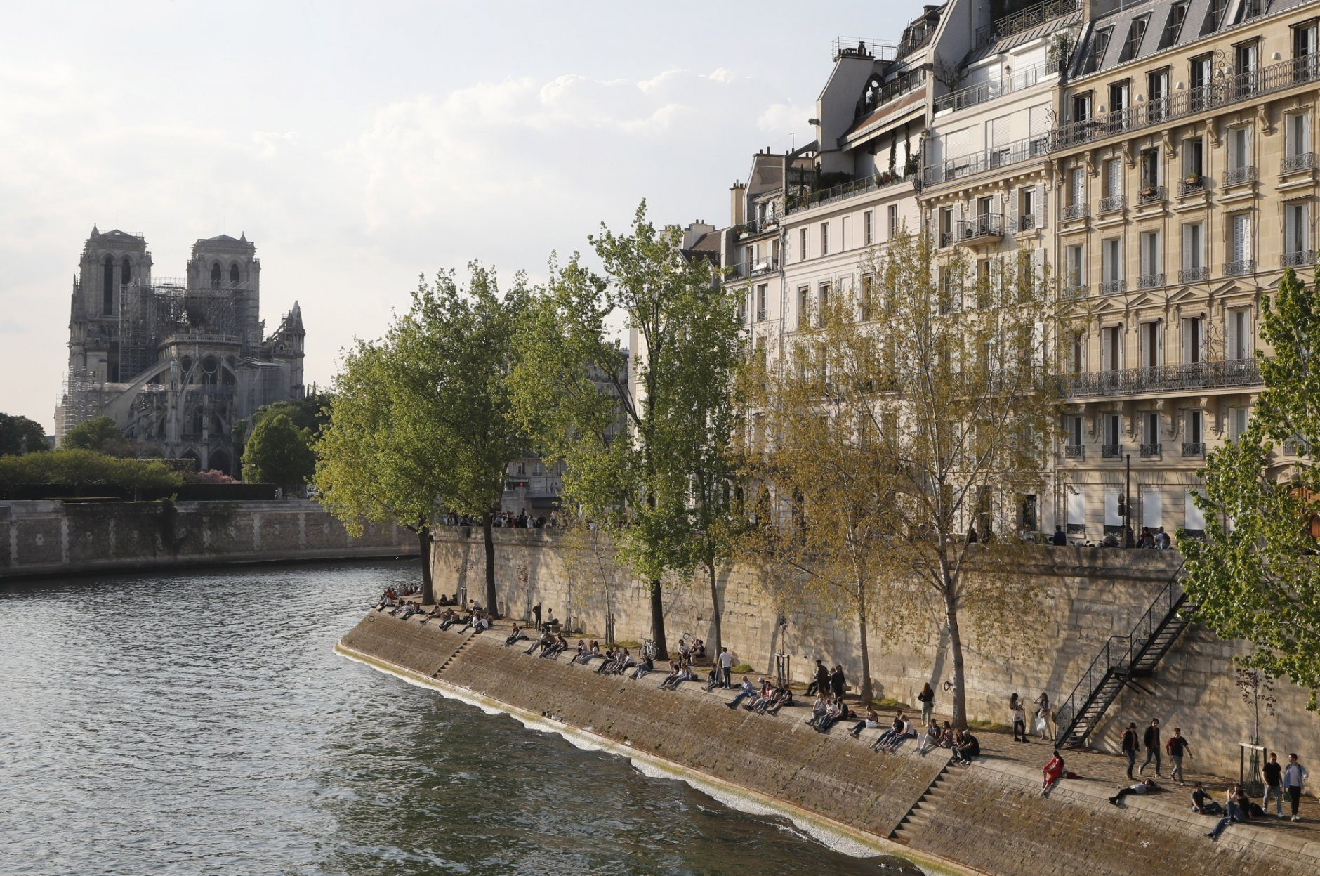People enjoy the sun next the Notre Dame Cathedral along the Seine river in Paris, Friday, April 19, 2019. Rebuilding Notre Dame, the 800-year-old Paris cathedral devastated by fire this week, will cost billions of dollars as architects, historians and artisans work to preserve the medieval landmark. (AP Photo/Michel Euler)