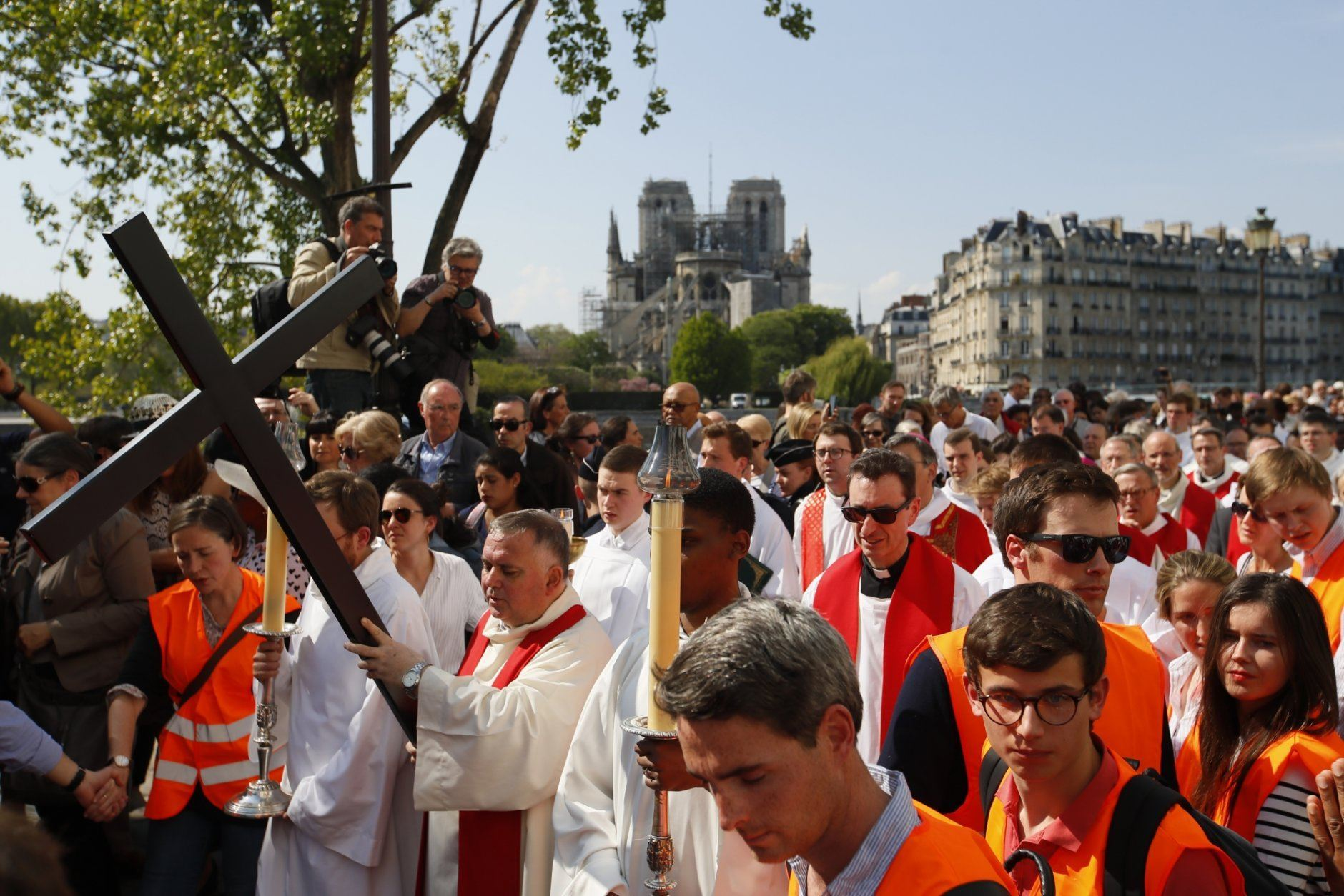 With Notre Dame cathedral in background, religious officials carry the cross during the Good Friday procession, Friday, April 19, 2019 in Paris. Top French art conservation officials say the works inside Notre Dame suffered no major damage in the fire that devastated the cathedral, and the pieces have been removed from the building for their protection.(AP Photo/Francois Mori)