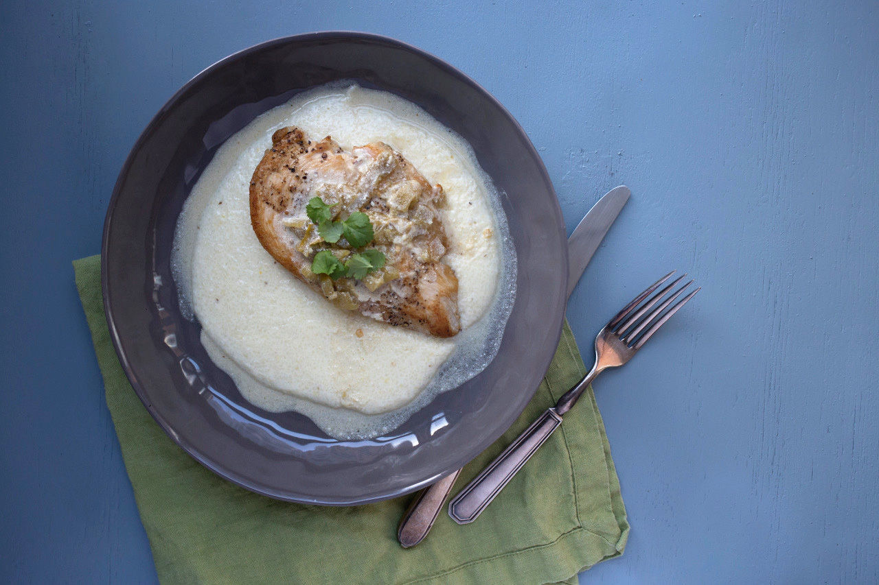 This December 2017 photo shows grits with chicken and tomatillo green chili and sour cream pan sauce in New York. This dish is from a recipe by Katie Workman. (Lucy Beni via AP)